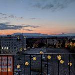 """Un coucher de soleil à Genève, avec l'affiche de """"L'Initiaive pour des multinationales responsables"""" en vue."""